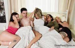 Jeune homme avec quatre femmes au lit après le mariage